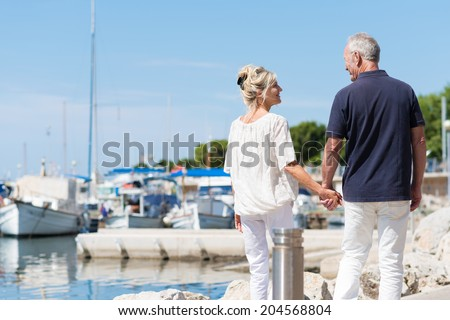 Mature couple enjoying a day at the coast walking away from the camera hand in hand past a small boat harbour - stock photo