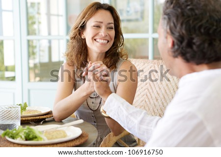 Mature couple enjoying lunch in a hotel terrace, holding hands. - stock photo
