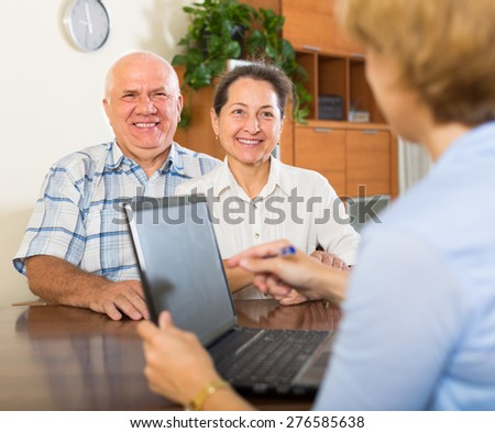 Mature couple filling questionnaire for saleswoman with laptop  - stock photo