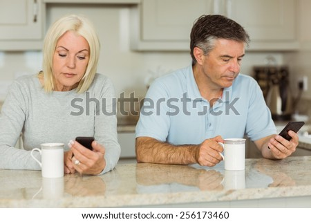Mature couple having coffee and using phones at home in the kitchen - stock photo