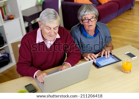 Mature couple having fun with tablet and computer - stock photo
