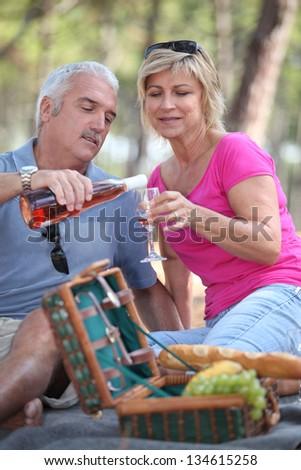 mature couple having picnic - stock photo