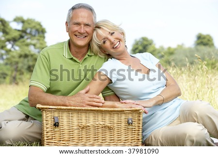Mature couple having picnic in countryside - stock photo