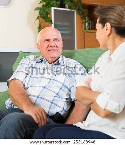 mature couple having serious talking in home interior - stock photo