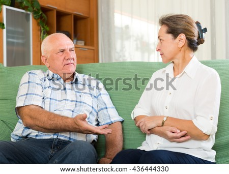 mature couple having serious talking in home interior. Focus on man - stock photo