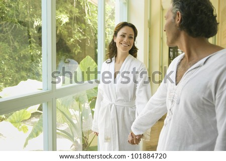 Mature couple holding hands at home, by large garden doors.