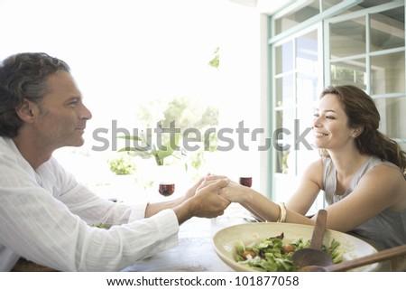 Mature couple holding hands while having lunch at their vacation home.