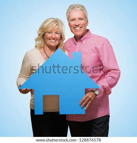 Mature Couple Holding Model Of A House against a blue background - stock photo