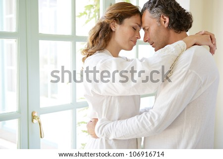 Mature couple hugging in a garden corridor at home, with their heads together. - stock photo