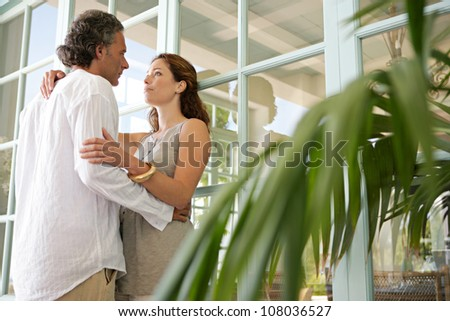 Mature couple hugging in a home terrace with large french doors.