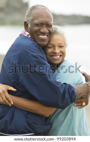Mature Couple Hugging on Beach - stock photo