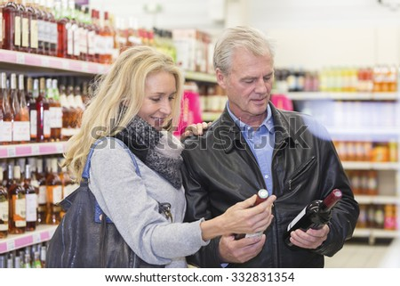 Mature couple in a supermarket choosing a wine bottle