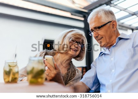 Mature Couple In Cafe Watching Pictures Of Their Grandchildren On Smart Phone - stock photo
