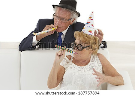 Mature couple in  push out party hats blowing noise-makers. - stock photo