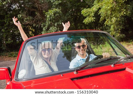 Mature couple in red cabriolet on sunny day cheering at camera - stock photo