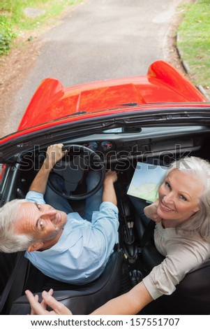 Mature couple in red classy convertible looking up at camera