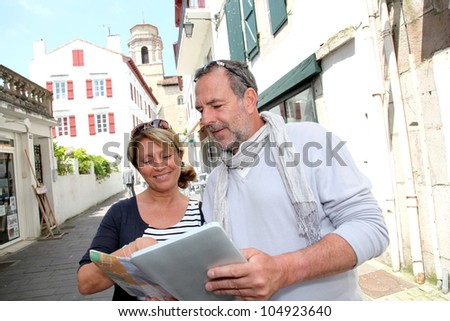 Mature couple in seaside resort looking at map - stock photo