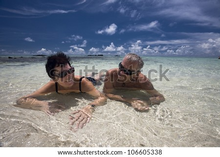 mature couple is lying together on a white sand beach, tropical beach in Mauritius