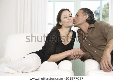 Mature couple kissing while sitting by large garden doors in living room.