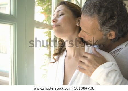 Mature couple kissing while standing by large garden doors at home. - stock photo