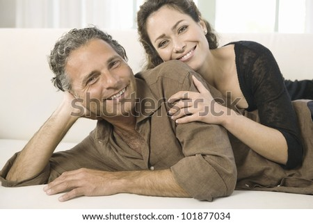 Mature couple laying down on a white sofa, smiling at the camera. - stock photo