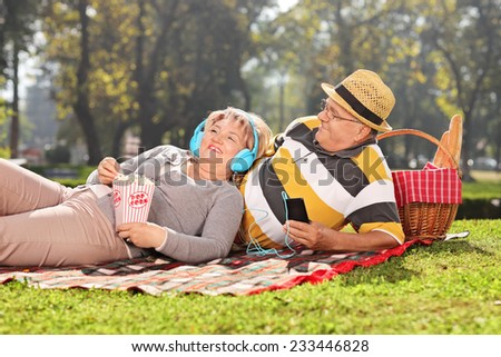 Mature couple listening music on headphones in park on a sunny day