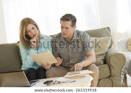 Mature couple looking at document while calculating finances on sofa at home - stock photo