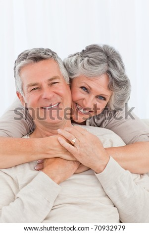Mature couple looking at the camera at home