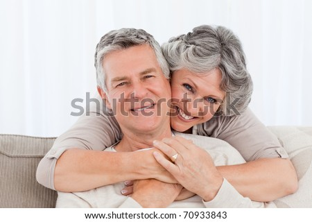 Mature couple looking at the camera at home - stock photo