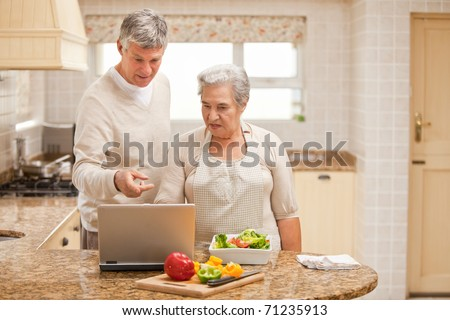 Mature couple looking at their laptop - stock photo