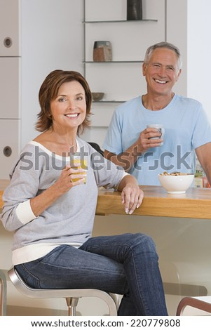 Mature couple looking to camera while having a healthy breakfast - stock photo