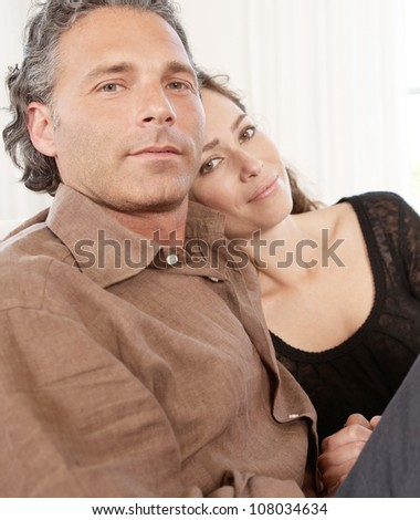Mature couple lounging on white sofa at home. - stock photo