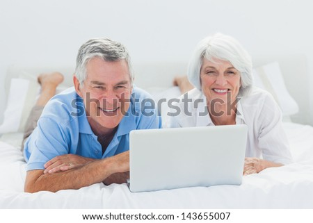 Mature couple lying and using a laptop in bed