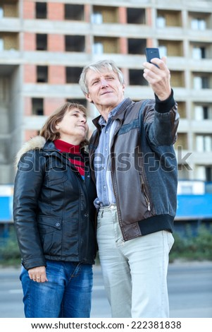 Mature couple making selfie standing together - stock photo