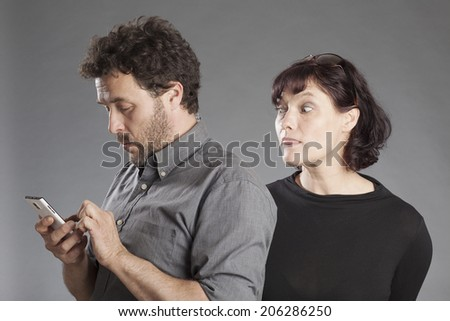 Mature couple man busy using smartphone woman looking curiously over man's shoulders - stock photo