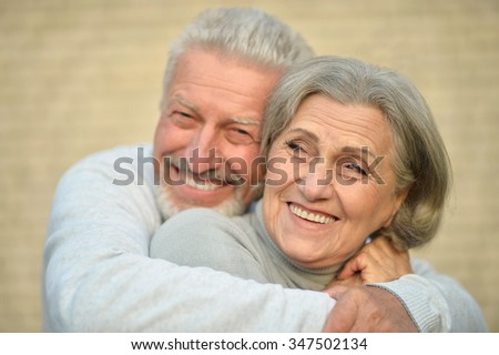 Mature couple near wall in the room