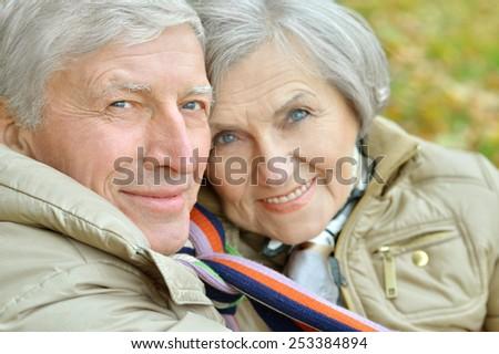 Mature couple near wall on street - stock photo
