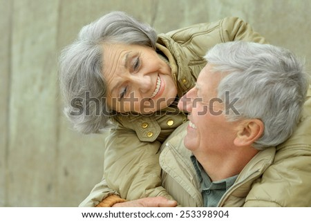 Mature couple near wall on street - stock photo