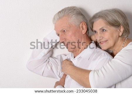 Mature couple near white wall on a white background