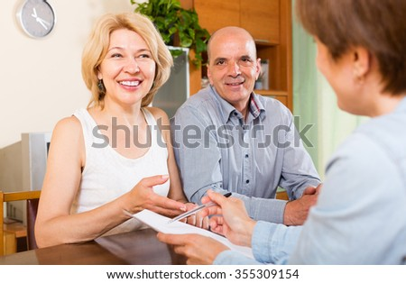 Mature couple of pensioners talking with employee at office - stock photo