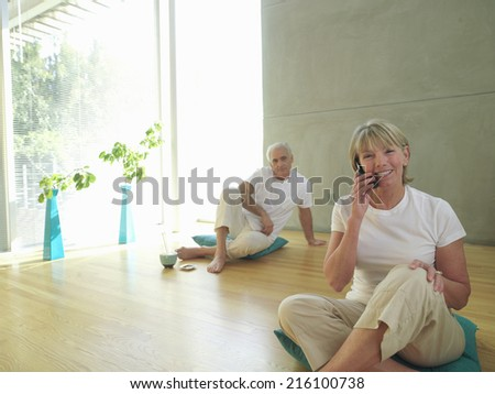 Mature couple on cushions, woman on telephone, smiling, portrait - stock photo