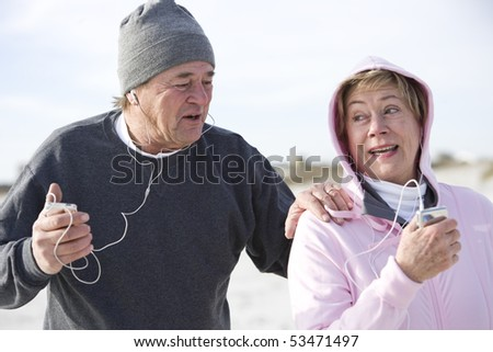 Mature couple outdoors listening to music on mp3 players - stock photo