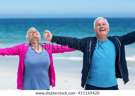 Mature couple outstretching their arms together on the beach - stock photo