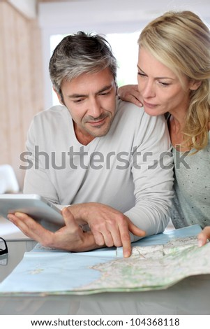 Mature couple planning vacation trip with map and laptop - stock photo