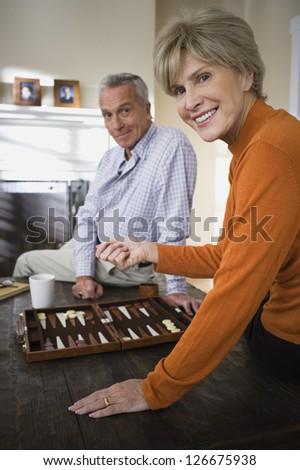 Mature couple playing backgammon - stock photo