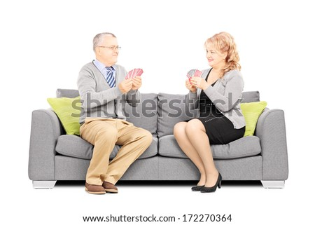 Mature couple playing cards and sitting on sofa, isolated on white background