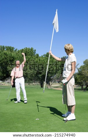 Mature couple playing golf, man punching air in delight at successful putt, woman holding flag on putting green - stock photo