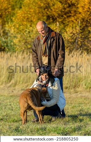 Mature couple playing with retriever dog autumn sunny park - stock photo