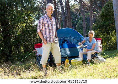 Mature couple posing on their campsite - stock photo