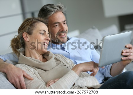Mature couple relaxing in sofa and using digital tablet - stock photo